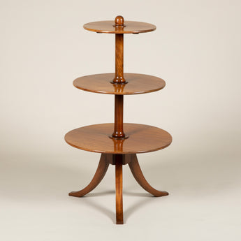 A three tier mahogany dumb-waiter with a tripod base, North European 19th century (base associated).