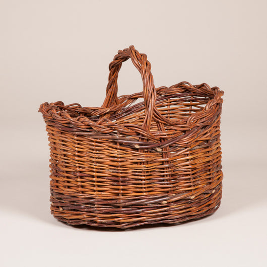 An oval caned basket with a handle.