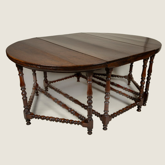 An early 18th century walnut table in three self-supporting parts with turned legs and stretchers; a central four-legged rectangular section with flanking three-legged demi-lunes. European, possibly Spanish.