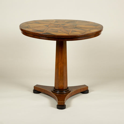 A round pedestal table, the early 19th century top with star-shaped geometric marquetry in exotic woods. Modern pedestal base.