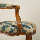 A Louis XV walnut fauteuil covered with floral grospoint needlework. The chair French provincial, circa 1760, the needlework late 18th or early 19th century.