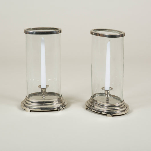 A pair of oval cylinder glass storm lanterns on silver bases.