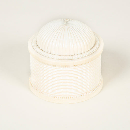 A 19th century round finely carved bone box with a domed screw lid.