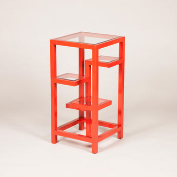 A red lacquered square etagere with staggered glass shelves. Mid-20th century French, redecorated.