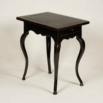 A charming small Louis XV darkened fruitwood table with a rectangular leather-lined top, drawer and cabriole legs. French, circa 1760.