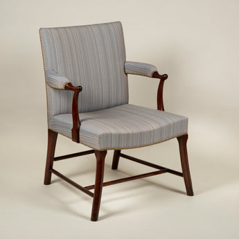 A substantial mahogany upholstered open arm chair with 'cockpen' shaped arms and legs. 19th century.