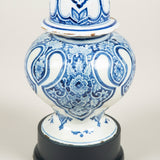 A pair of unusual squat blue and white Delft vases and covers, 19th century, mounted on plinth bases.