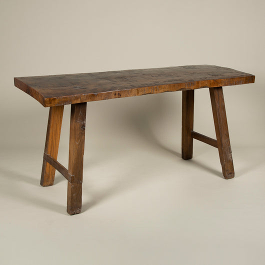A polished beech-wood shepherd's table with plank top and four splayed legs. Mid-20th century, East European.