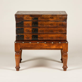 A low table in the form of a pile of books on a stand, the top book a lid over a fitted interior. 19th century French.