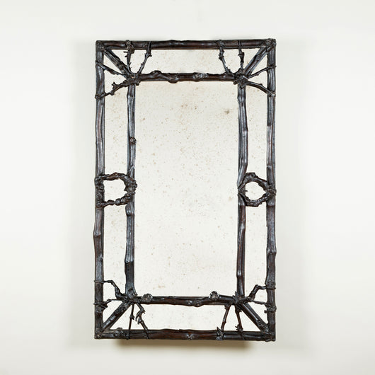 A rectangular mirror with a bordered mirror-glass and rustic twigwork frame. French, late 19th or early 20th century.