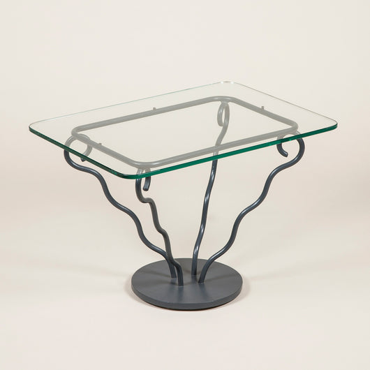 A pair of low 1950's painted iron tables, the rectangular top frame with four splayed serpentine supports and solid circular base. Replaced glass.