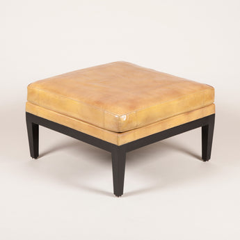 A square leather upholstered stool with ebonised legs. In the style of Jean Michel Frank.