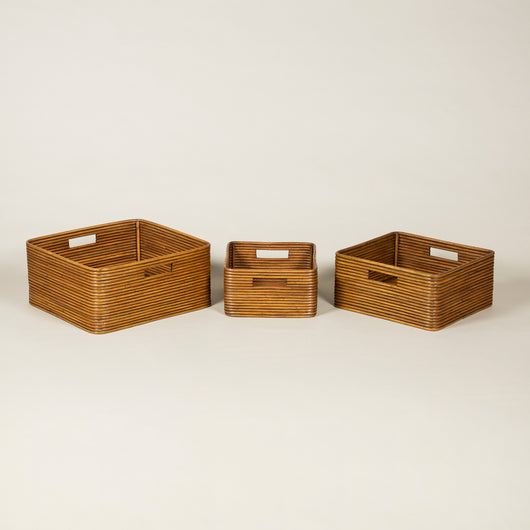 A set of three graduating square bamboo baskets or receptacles.