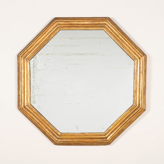 An octagonal mirror with a moulded gilt wood frame, probably mid 20th century.