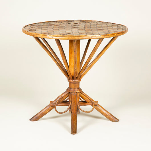 A round cane table with a chequer weave top and waisted understructure with four decorative cane loops and four feet. 20th century.