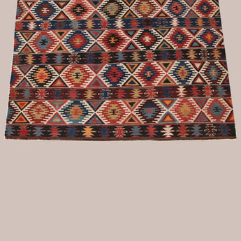 A patterened Caucasian kilim in reds, blues and browns, mid-20th century.