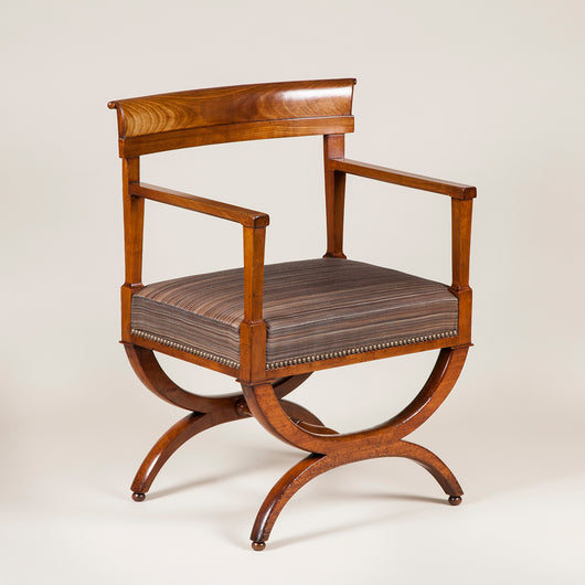 A pair of mahogany open armchairs of unusual wide proportions with cross-frame legs. French, circa 1800.