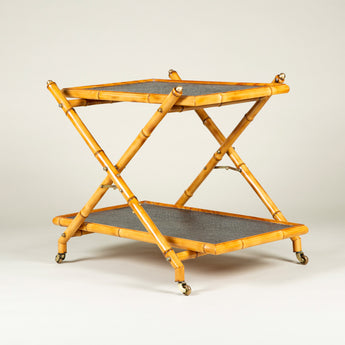 A mid-20th century French faux-bamboo table with two lined tiers mounted on brass castors. Circa 1960.