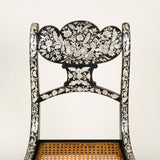 A set of six penwork decorated Regency dining chairs with shaped backs and sabre legs, circa 1820.