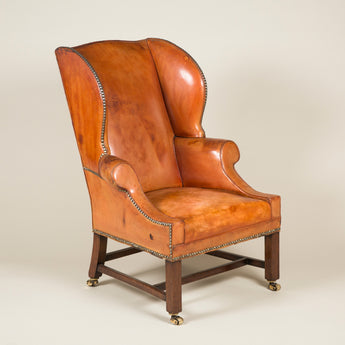 A pair of leather covered wing armchairs with chamfered square section legs, early 20th century.