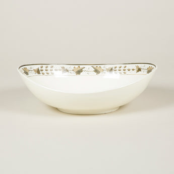 An oval white glazed pottery bowl with a band of leaf decoration to the inside.