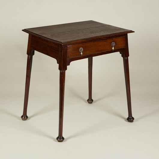 A late 19th century Arts and Crafts movement small oak side table with a drawer and four splayed legs with pad feet.