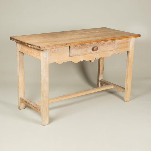 A late 19th century French pinewood side table with a single drawer and pretty shaped apron.