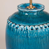 A turquoise pot with thumb printing design to the rim wired as a lamp. 20th century studio pottery.