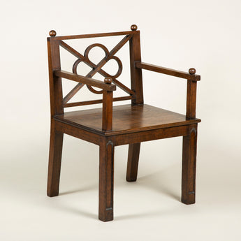 A pair of early 20th century oak hall chairs with arms and simplified Gothick detailing, including a quatrefoil open fret to the back, in the manner of Lutyens