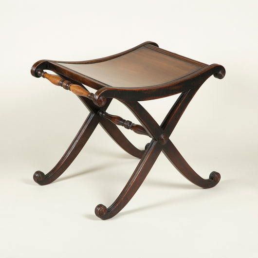 A late Regency mahogany x-frame stool with a saddle seat and turned supports, circa 1820.