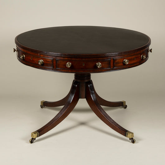 A Regency English revolving drum table with a leather lined top over four drawers and four blind drawers the central support on four splayed legs. Circa 1810.