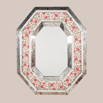 An early to mid-20th century Venetian mirror, rectangular with canted corners, with a band of floral silk embroidery inset under glass in the mirror-bordered frame.