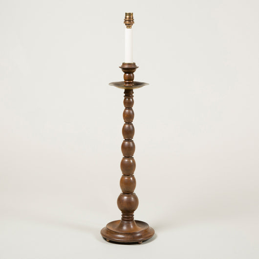 A pair of turned hardwood candlesticks with circular metal drip trays and circular bases, wired for electricity.