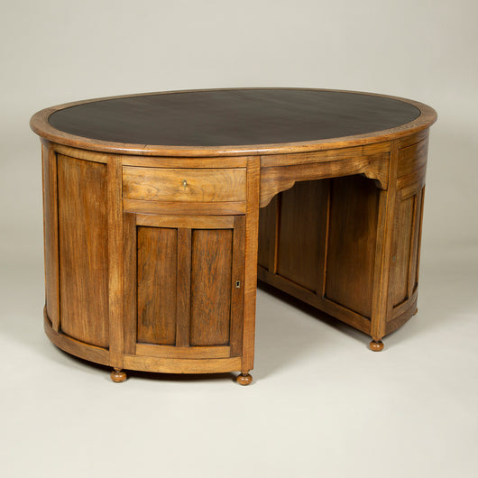 A early 20th century oval teak partner's desk with a leather lined top.