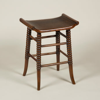 An elegant and well-made walnut stool, the dished seat with carved scroll sides, and the bobbin-turned legs with splayed feet. Late 19th century.