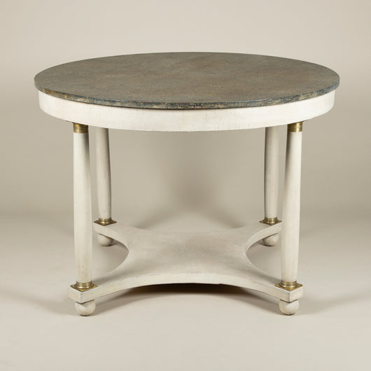 A late 19th century round centre table in the Empire style with a painted faux granite top raised upon four column legs with brass mounts and a concave stretcher on bun feet. France circa 1890.
