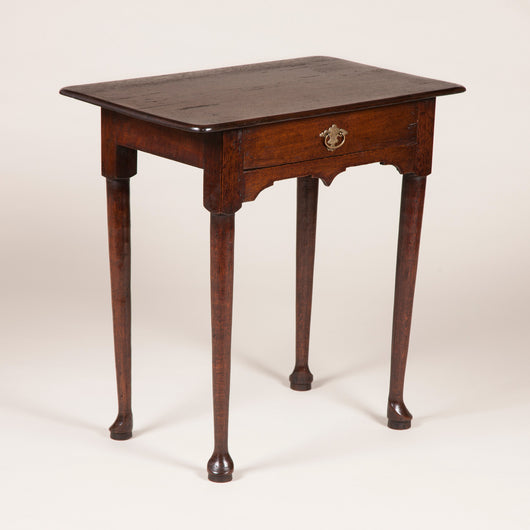 A small mid-18th century oak side table with a drawer, shaped apron and round tapering legs with pad feet.