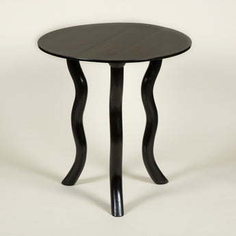 A solid ebony round tripod table with serpentine legs.