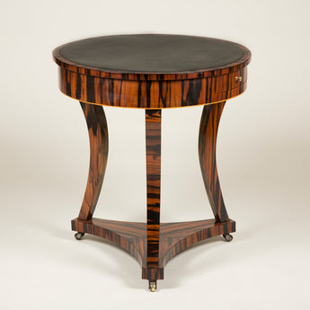 A small early 19th century calamander wood drum table with a leather lined top and three sabre legs on an incurved triform base. English circa 1820.