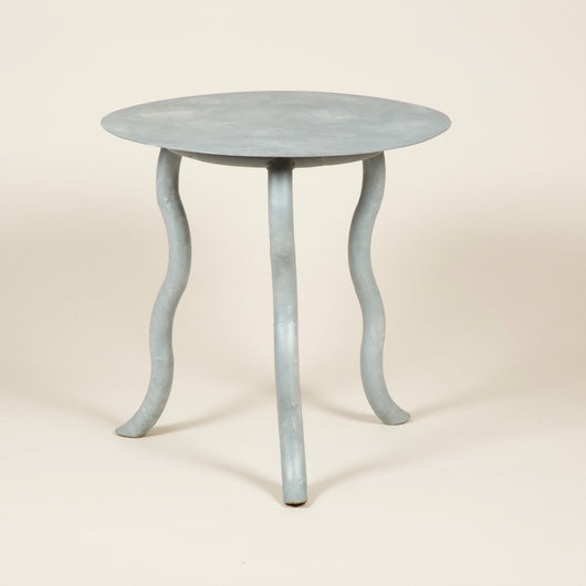 A grey painted iron table with three serpentine legs and a round top. 20th century French.