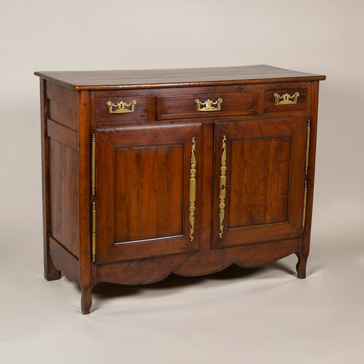 A late 18th century French yew and elmwood buffet with three short drawers over a cupboard with two doors.