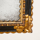 A 17th century Spanish black and gilt carved wood frame with later mirror glass.