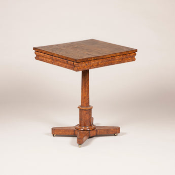 An early 19th century burr elm occasional table with a tambour frieze and pedestal base.