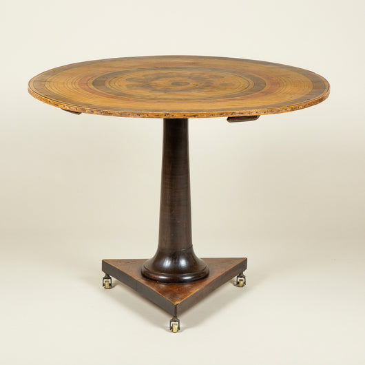 A French Directoire pedestal table with a round painted canvas-convered tilt top, the mahogany base with a simple flared column on a triangular foot with brass castors. Circa 1800.