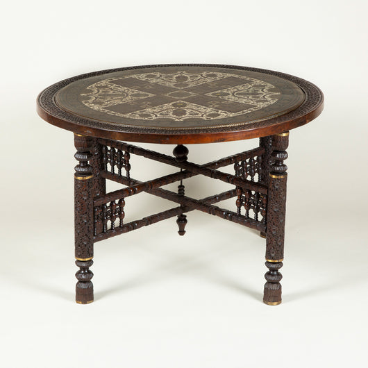A low round table, the enamelled and engraved brass top inset in a hardwood frame on a folding hardwood base. Late 19th or early 20th century. Possibly Anglo-Indian.