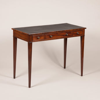 A small and elegant George III mahogany writing table with a leather-lined top and three frieze drawers, on four square section tapering legs, circa 1790.