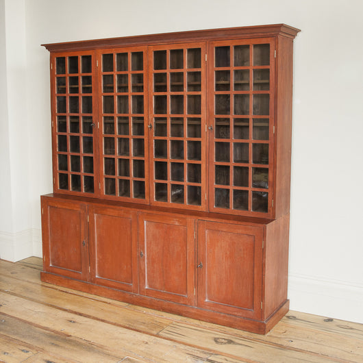 A painted bookcase of pleasing proportions with four square-glazed upper doors and simple panelled doors beneath, circa 1910.