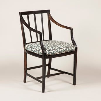 Eight Sinhalese ebony elbow chairs with stick backs and caned seats. £4600 per pair.