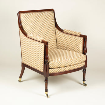 A George III mahogany-framed library chair, with canted corners to the top of the square back and elegant baluster-turned arm supports and front legs. Circa 1800.