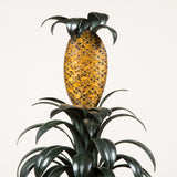 A tole wall decoration in the form of a stylised pineapple with foliage in a red and gilt planter.